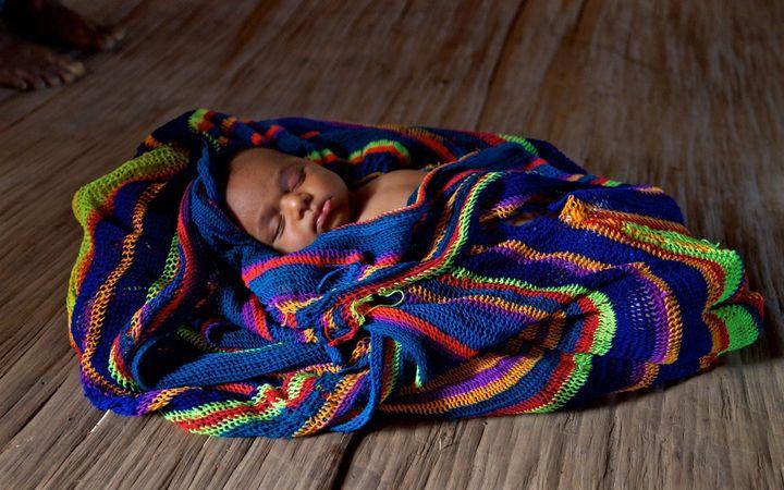 Sibilato's newborndaughtersleeps in a traditional woven bilum. Bosavi region, Southern highlands, Papua New Guinea.
