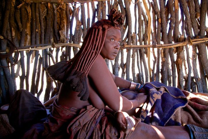 TheHimba, a powerful women's circle,have created a safe and comfortable environment for thismother in a small mud hut. Kaokoland region, Namibia.