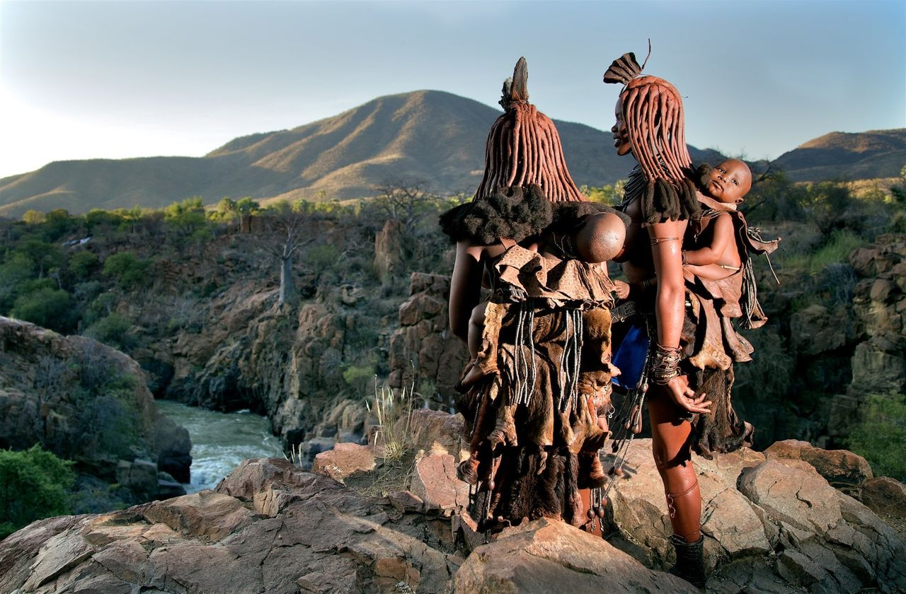 Young mothers carry their babies in traditional carriers looking over the Kunene river. Himba tribe, Namibia.