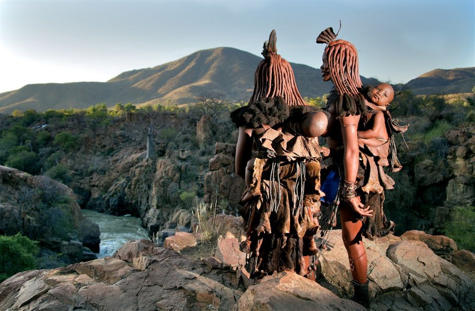 Young mothers carry their babies in traditional carriers looking over the Kunene river. Himba...