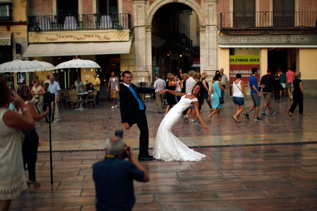 A newly married couple poses at La Constitucion square in Malaga, Spain, on July 11,
