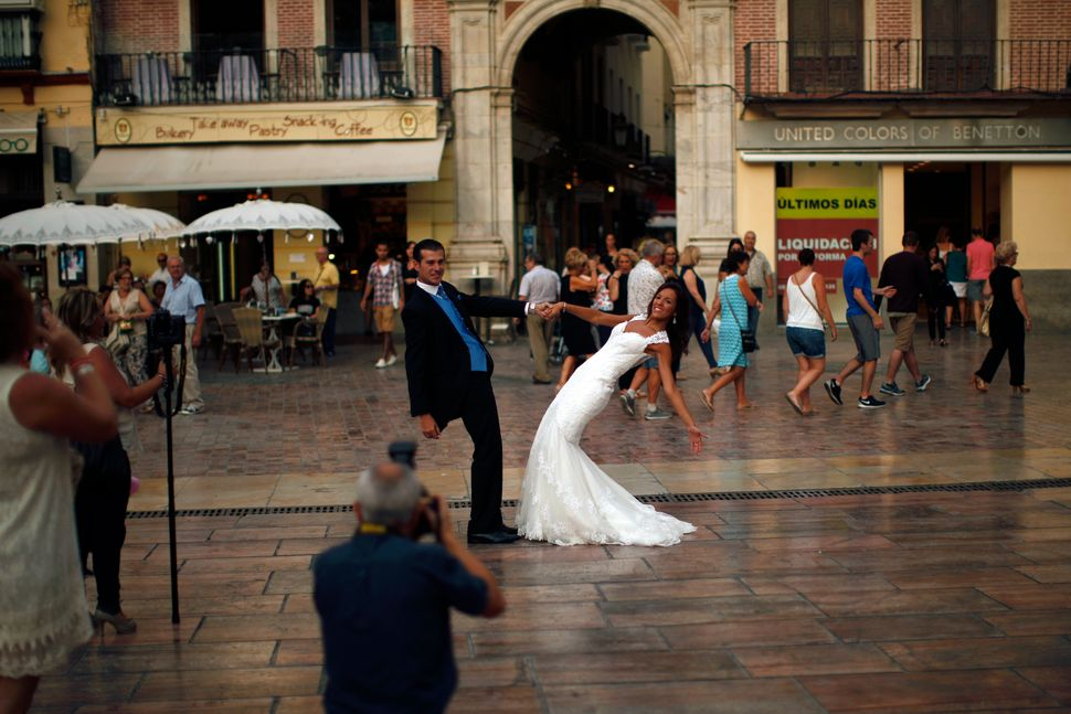 A newly married couple poses at La Constitucion square in Malaga, Spain, on July 11, 2014.