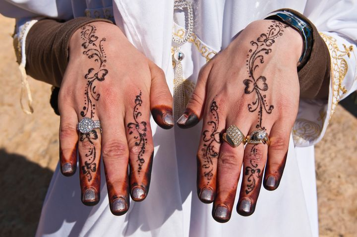 Recently married Hergueme Takwashows off her hennaed hands in Tozeur, Tunisia.