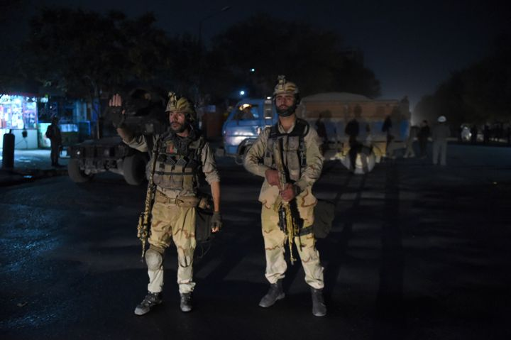 Afghan security personnels stands as they keep watch near the site of an attack by gunmen inside the Kart-e- Sakhi shrine in