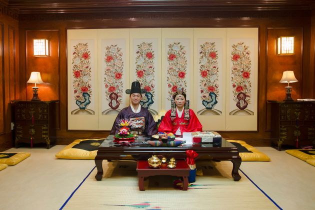 A couple poses in a traditional wedding hall in Anyang, South