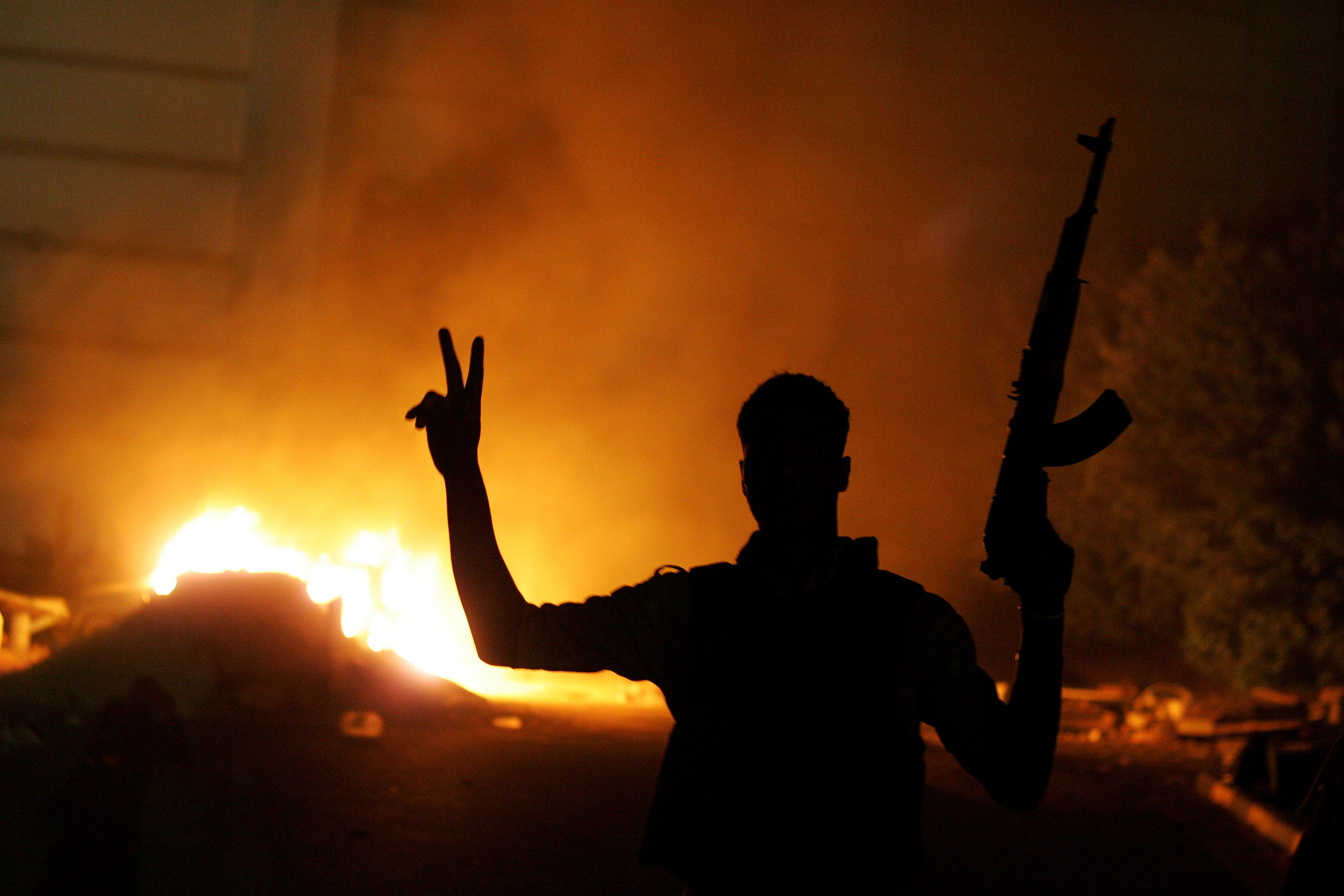 An armed libyan man flashes the victory sign in front of a fire at the hardline Islamist group Ansar el-Sharia headquarters on September 21, 2012 in Benghazi, Libya. Hundreds of Libyan protesters forced members of a hardline Islamist militia out of their base in the second city of Benghazi late on September 21, setting fire to and wrecking the compound. Members of the Salafist jihadi group Ansar al-Sharia fired in the air before being forced out of their base by the demonstrators. AFP PHOTO / ABDULLAH DOMA        (Photo credit should read ABDULLAH DOMA/AFP/GettyImages)