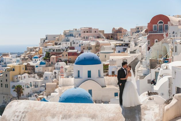 A married couple poses in Santorini,