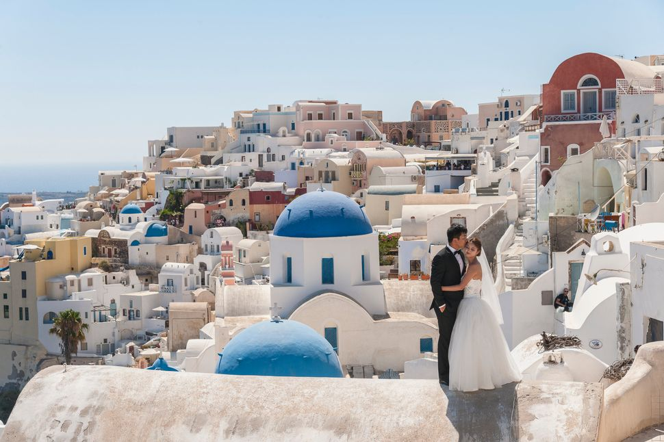 A married couple poses in Santorini, Greece.