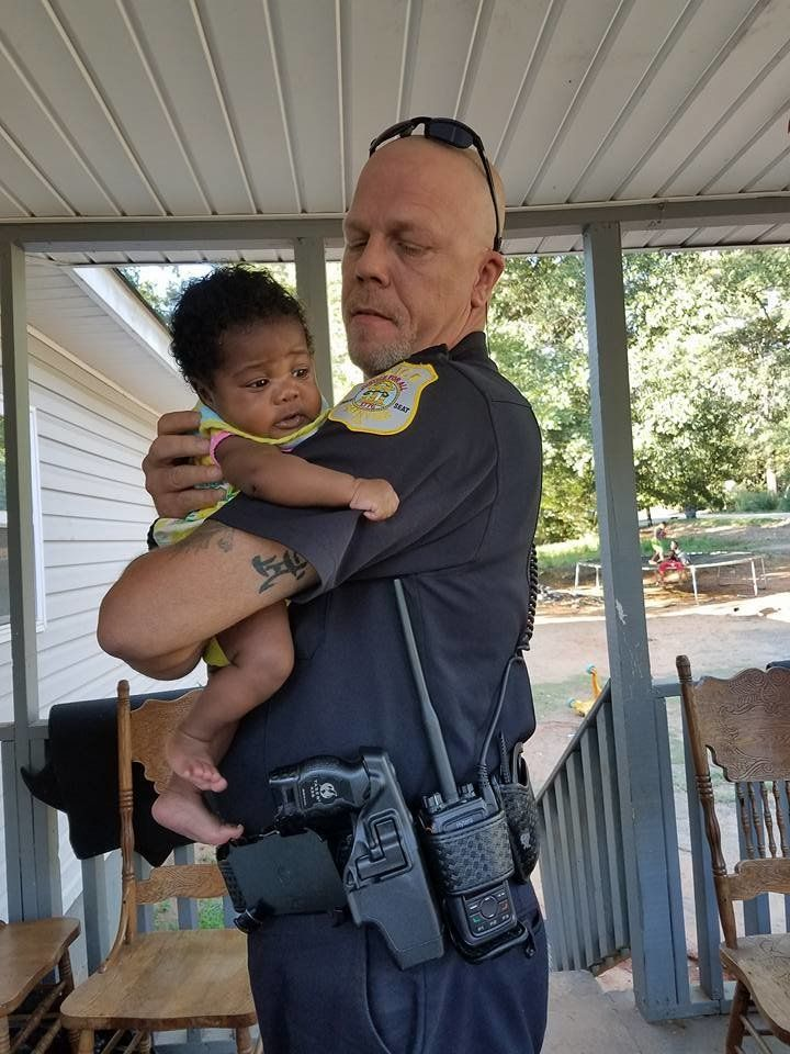 Two-month-old Ma'Yavi Parham with her godfather, Officer Kenneth Knox.