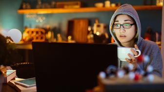 Young woman watching a movie, using laptop at home.