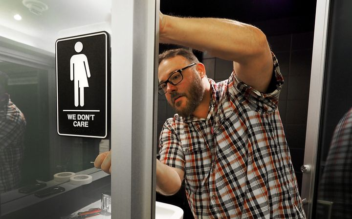 Museum manager Jeff Bell adheres informative backing to gender neutral signs in the 21C Museum Hotel public restrooms on May