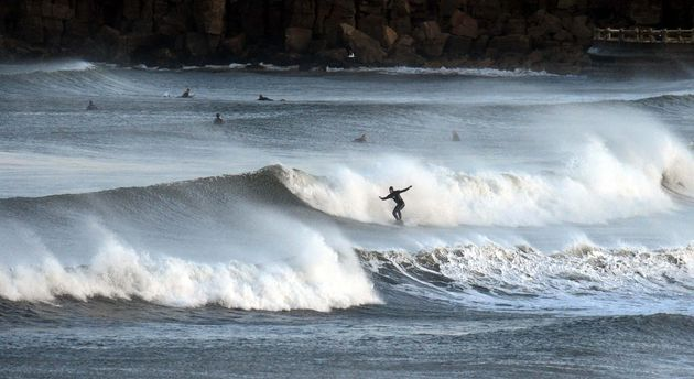 Surfers at Tynemouth enjoying the 'Indian summer' attributed to climate