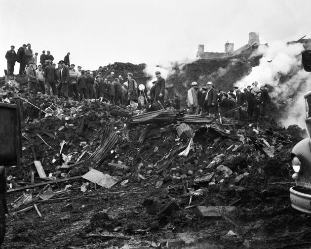 Rescue workers stand on the rubble which slid down the hill into the village of Aberfan on 21st October
