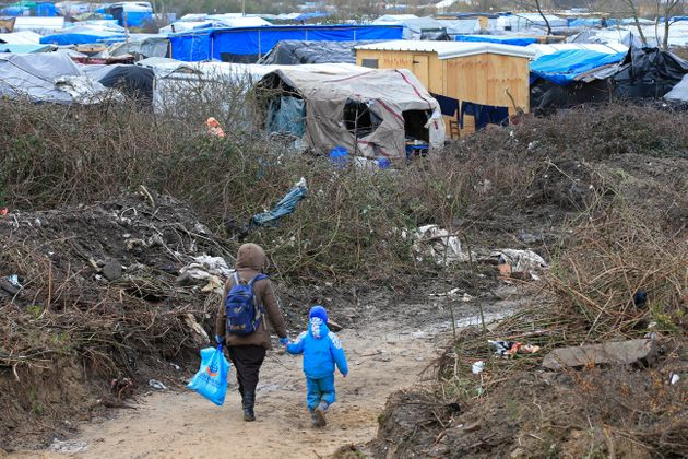 A migrant and her child walk in the Calais