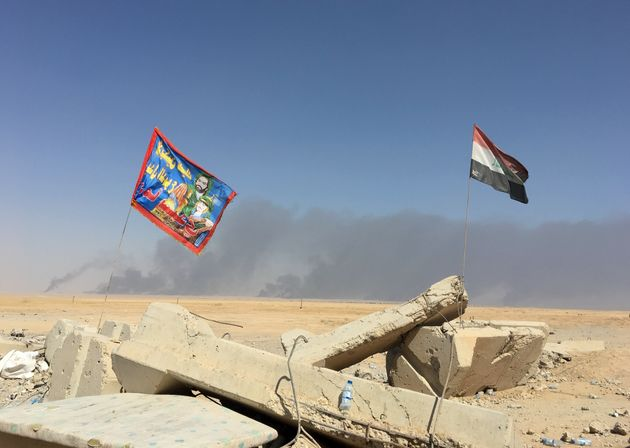 A Shiite militia flag flies next to the Iraqi flag next to Qayyarah Airfield West, where hundreds of...
