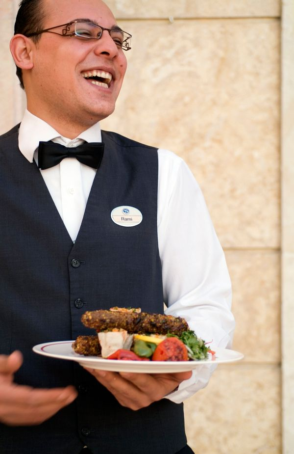 A waiter at theSheraton in Aleppo holds a plate of foodin 2010.