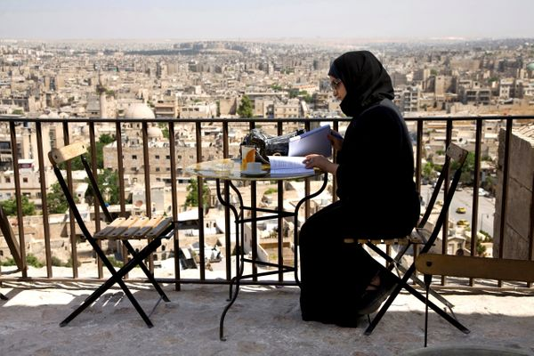 A woman sitsat atable in an Aleppobar on May 21, 2009.