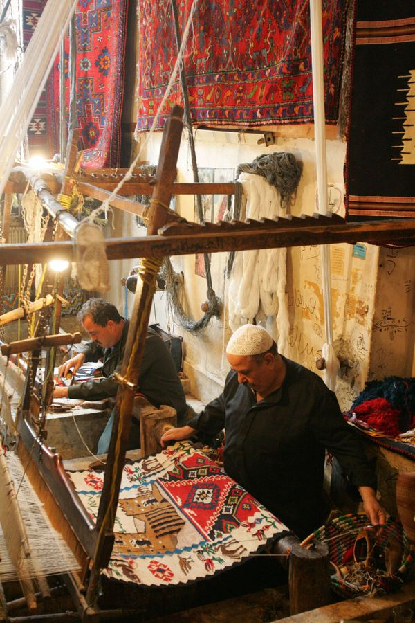 Syrian men weave traditional rugs in Aleppo on March 18, 2006.