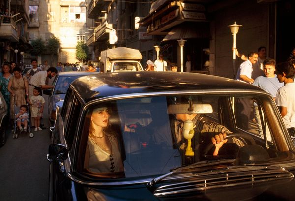 A couple stuck in a traffic jam on a bustling street in Aleppo on July 7, 1996.