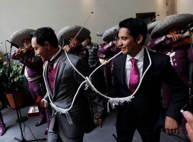 Newlyweds Diego, right, and Ricardo leave their wedding ceremony as a mariachi band plays on...