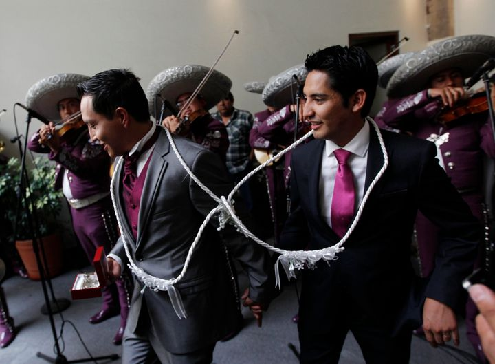 Newlyweds Diego, right, and Ricardo leavetheir wedding ceremony asa mariachi band plays on July 14, 2013 in Mexico City.