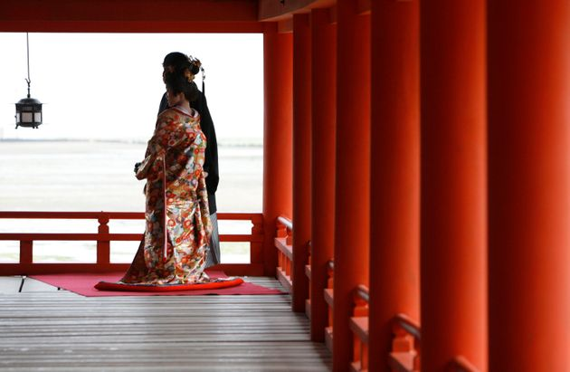 A bride and groom in traditional Japanese wedding attire pose for photos at Itsukushima Shrine in Hatsukaichi,...