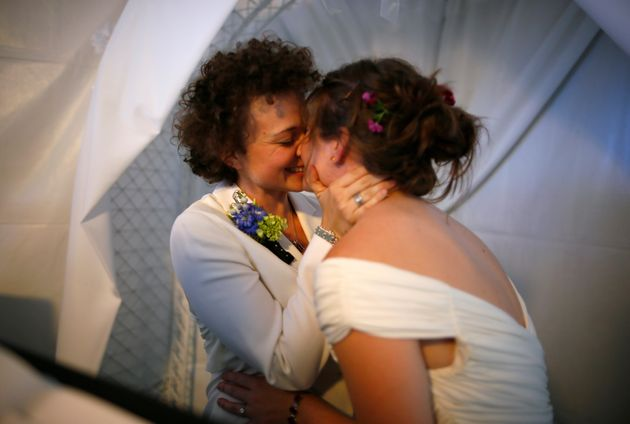 Anne Austin, 28, and Jen Durham, 30, kiss as they get married in West Hollywood, California, on July...