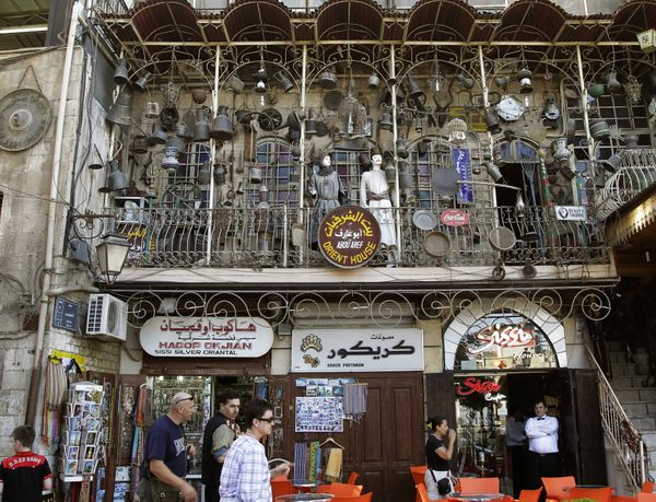 Tourists walk past a trinket shop in Aleppo on June 23, 2010.