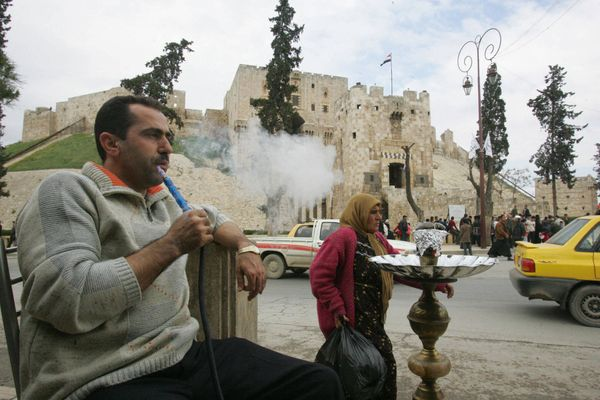 A man smokes his water pipe in front of the Aleppo citadelonMarch 18, 2006.