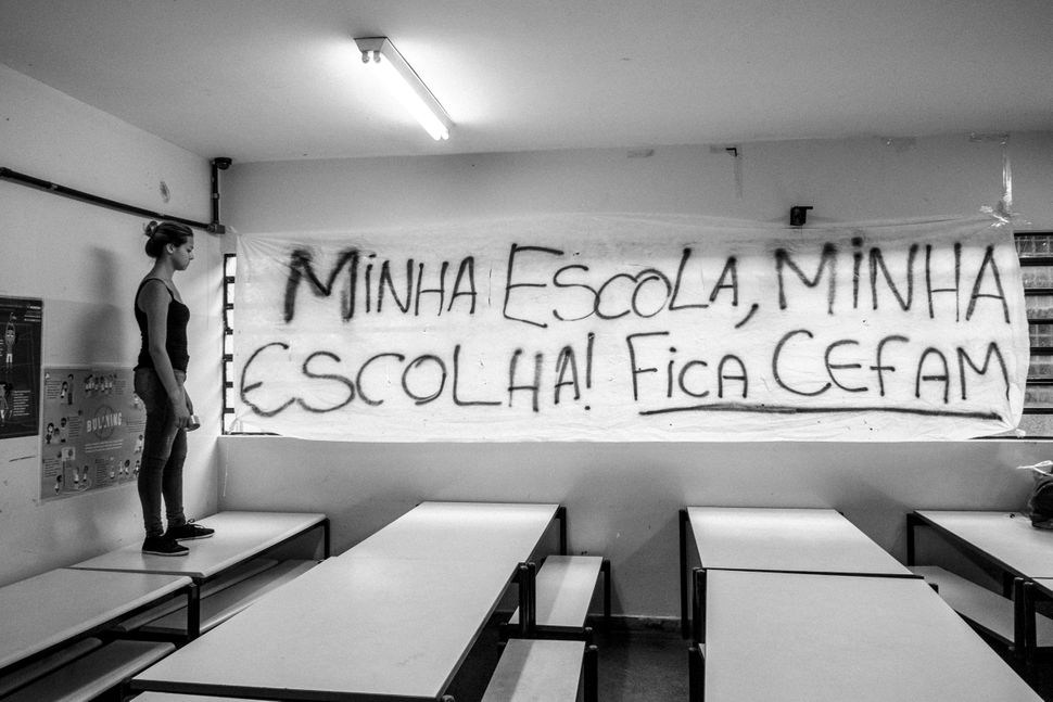 "A student stands inside a classroom at Cefam, a state school in Diadema, Sao Paulo. The banner reads: ""My school, my choice!"