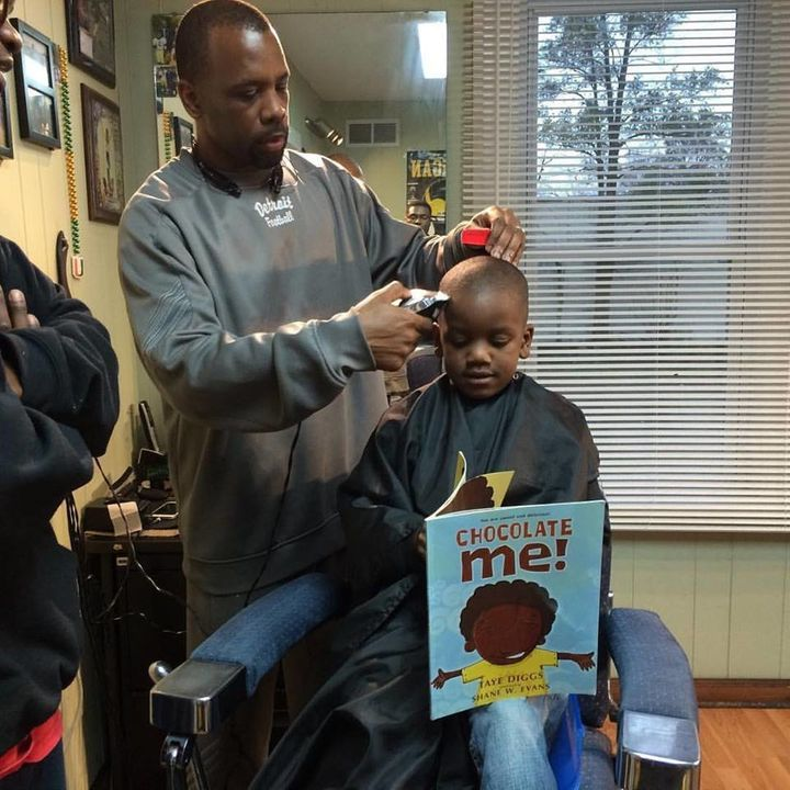 Ryan Griffin cutting a boy's hair while he reads aloud.