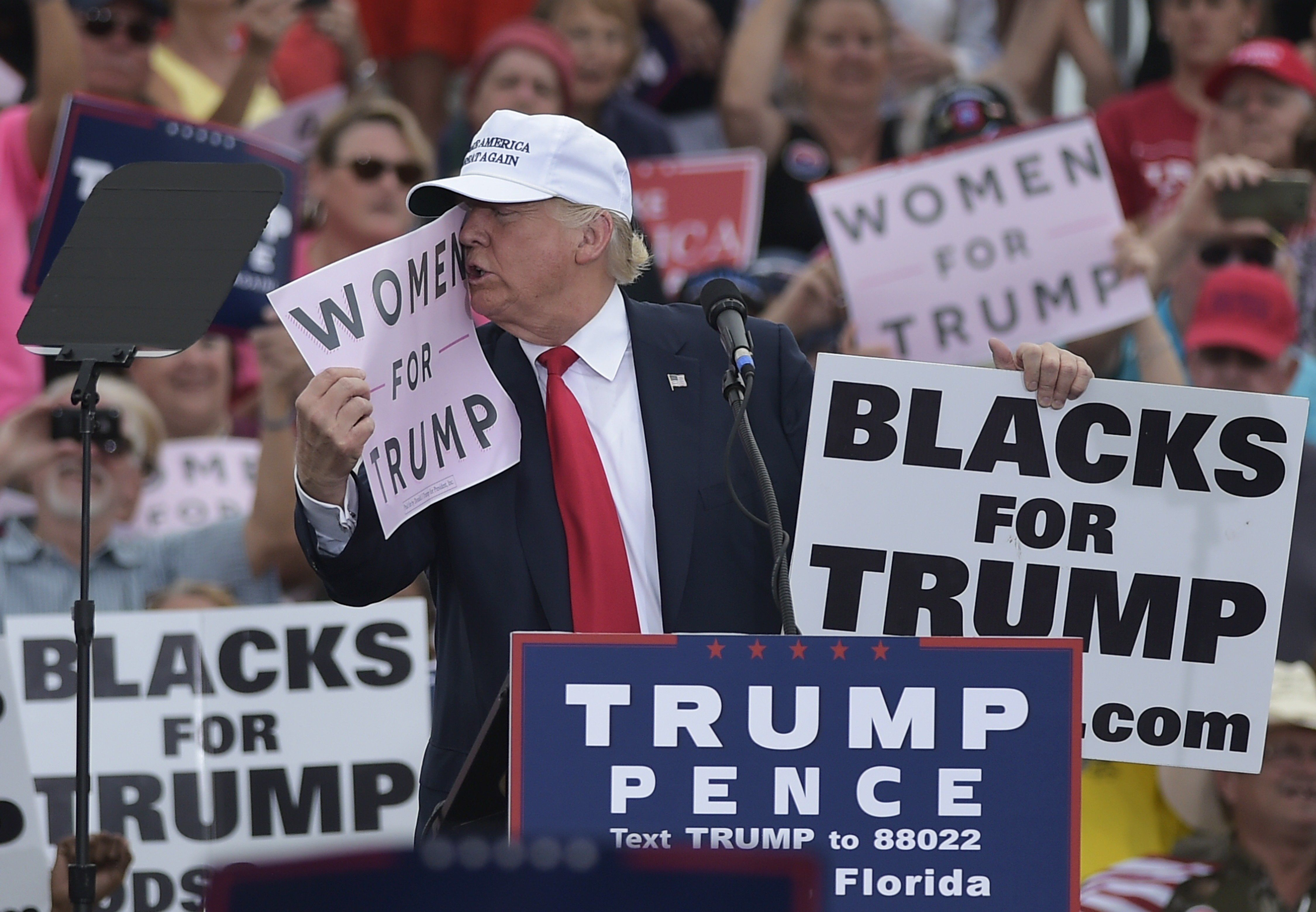 Republican presidential nominee Donald Trump kisses a 'Women for Trump' placard during a rally at the Lakeland Linder Regional Airport in Lakeland, Florida on October 12, 2016. / AFP / MANDEL NGAN        (Photo credit should read MANDEL NGAN/AFP/Getty Images)