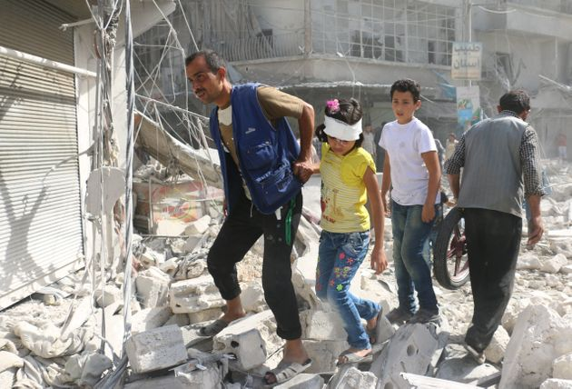 Syrians walk over rubble in