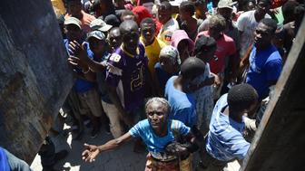 Hurricane Matthew victims receive food from the UN's World Food Programme in Roche-a-Bateaux, in Les Cayes, in the south west of Haiti, on October 12, 2016. The first major handout of food aid took place along Haiti's storm-wrecked southwest coast but supplies were still far short of what was needed by the thousands of starving people.  / AFP / HECTOR RETAMAL        (Photo credit should read HECTOR RETAMAL/AFP/Getty Images)