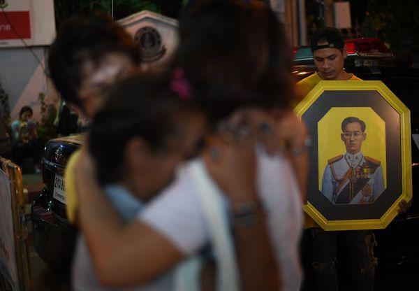 People react to the death of Thailand's King Bhumibol Adulyadej at Siriraj Hospital in Bangkok on October 13, 2016.