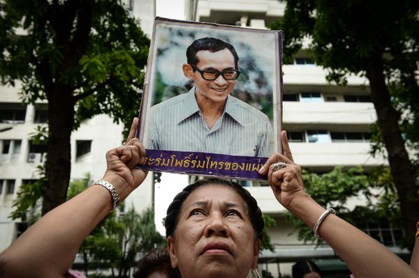A supporter of Thailand's King Bhumibol Adulyadej holds a picture bearing his image at Siriraj Hospital.