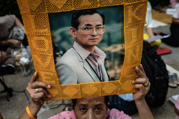 A supporter of Thailand's King Bhumibol Adulyadej holds a picture bearing his image.