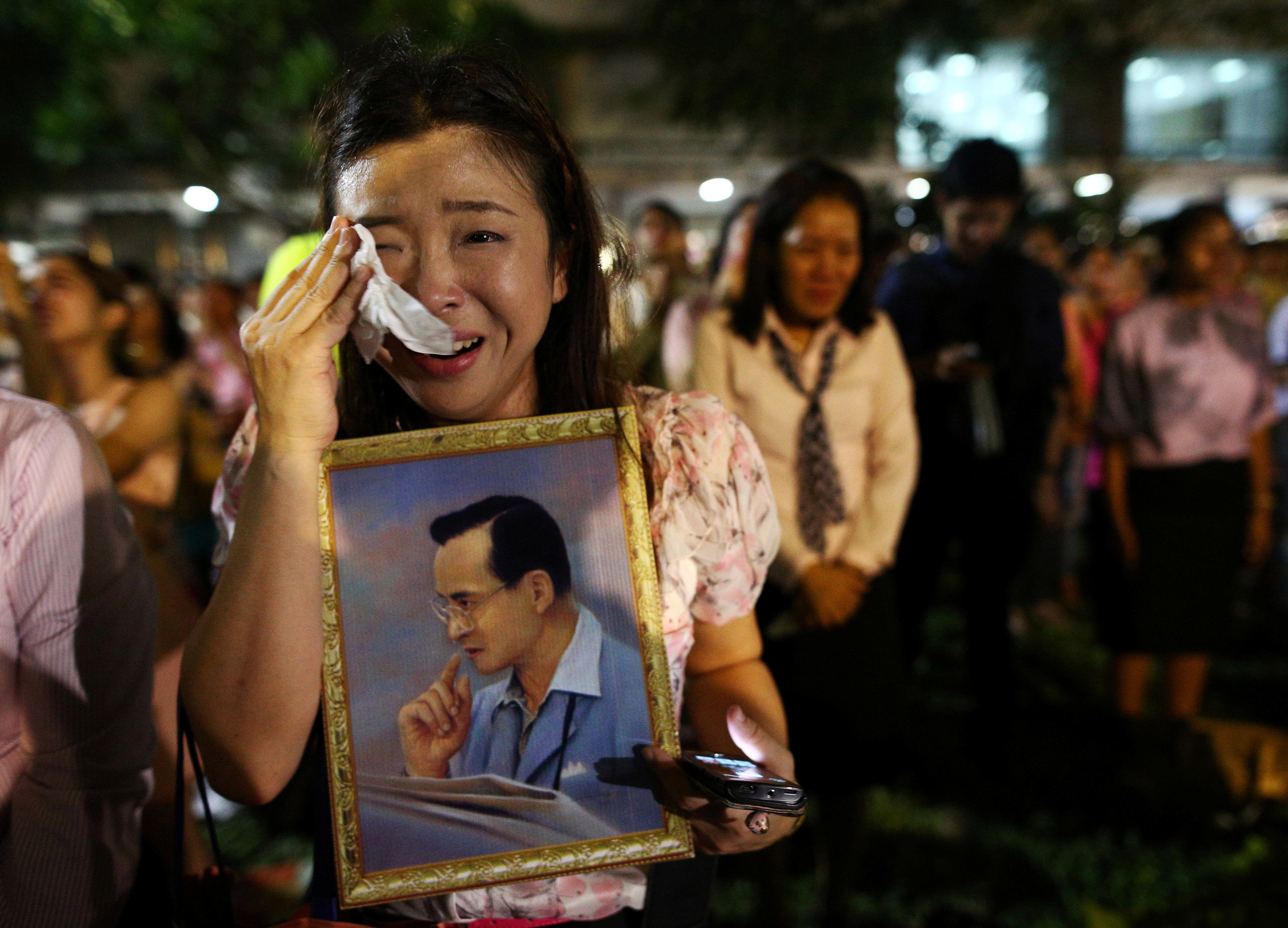 A woman weeps after an announcement that Thailand's King Bhumibol Adulyadej has died.