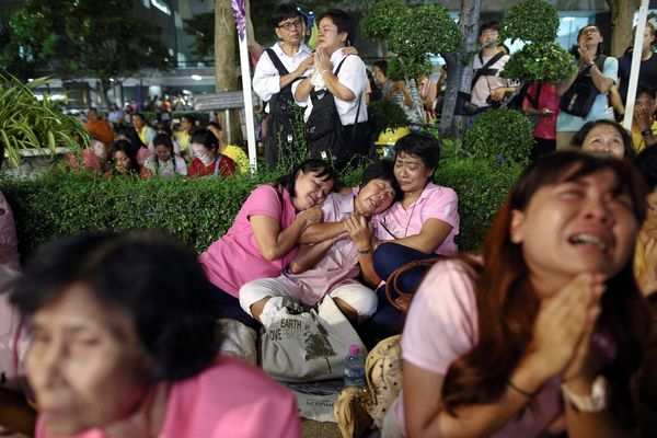 People weep after an announcement that Thailand's King Bhumibol Adulyadej has died.