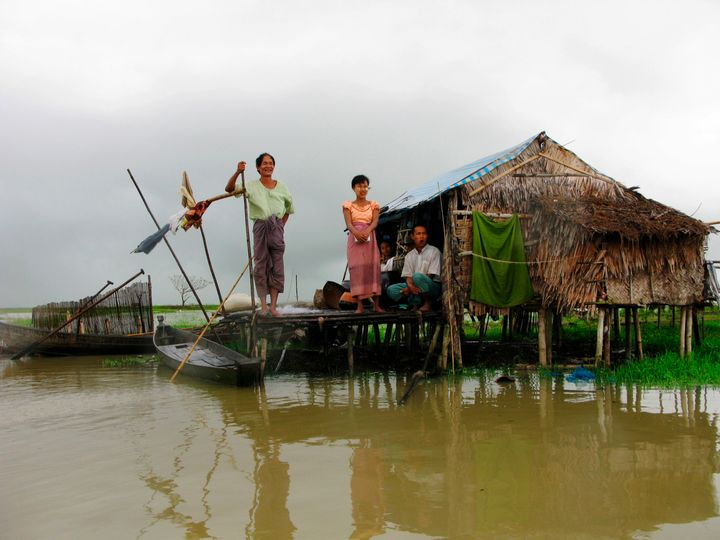 People look out from their hut, built of tarpaulin and bamboo, located on the swamp of Pay Kunhasay village, Kawhmu Township