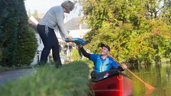 EDITORIAL USE ONLYDomino's delivery driver Robert Isuf paddles a canoe down the River Loose in Maidstone, Kent, to deliver fresh pizza to Debbie Hayes, as DominoÕs announces it is trialling a waterway delivery service in the canal side village.