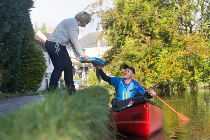 Robert Isuf paddles a canoe down the River Loose to deliver pizza to local woman Debbie Hayes.