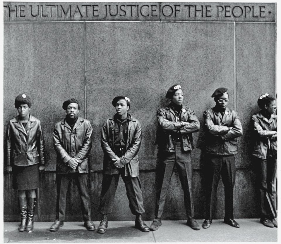 View of a line of Black Panther Party members as they stand outside the New York City courthouse under a portion of an Abraha