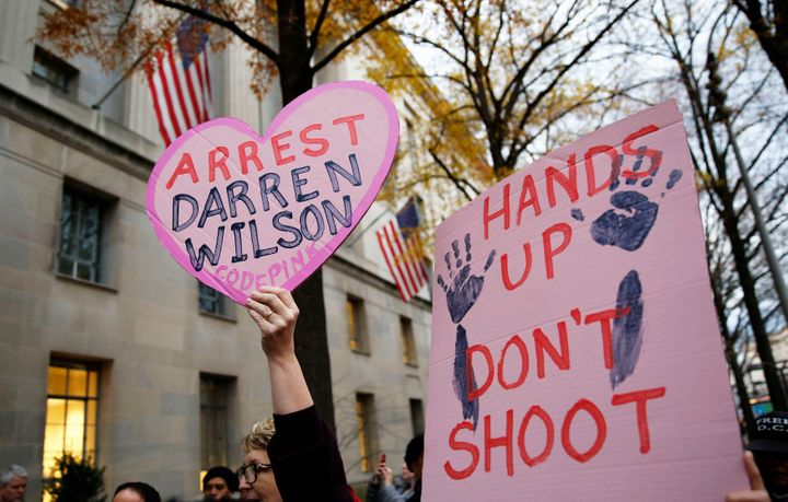 Protestors hold signs as they rally in 2014 against the grand jury exoneration of Officer Darren Wilson f