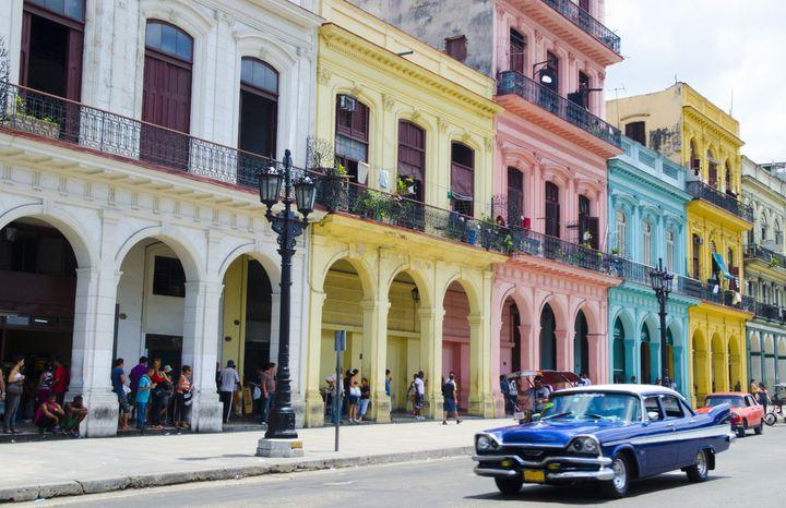 A car passes by pastel-colored buildings in Havana, Cuba.