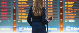 LUGGAGE TRAVEL PEOPLE TRAVELING BUSINESSWOMAN GIRLS WOMEN GLOBAL COMMUNICATIONS ARRIVAL DEPARTURE BOARD YOUNG ADULT ADULT FLYING COMMUTER CAUCASIAN