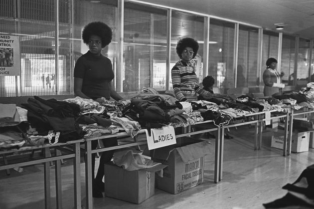 Members of the Black Panther Party stand behind tables ready to distribute free clothing to the public...