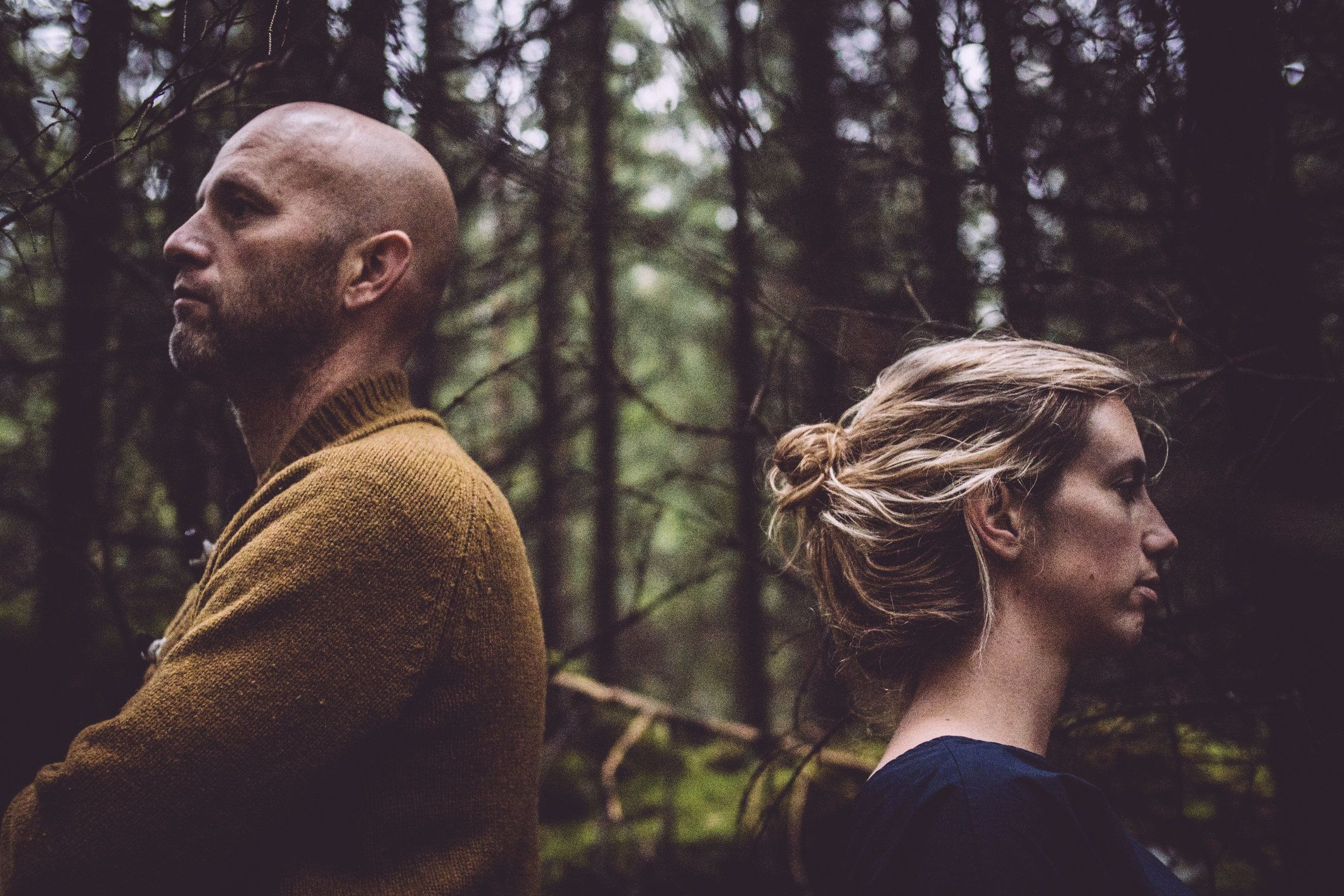 Couple with back to each other in forest