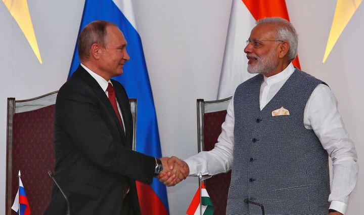Russian President Vladimir Putin (L) shakes hands with India's Prime Minister Narendra Modi during exchange of agreements eve