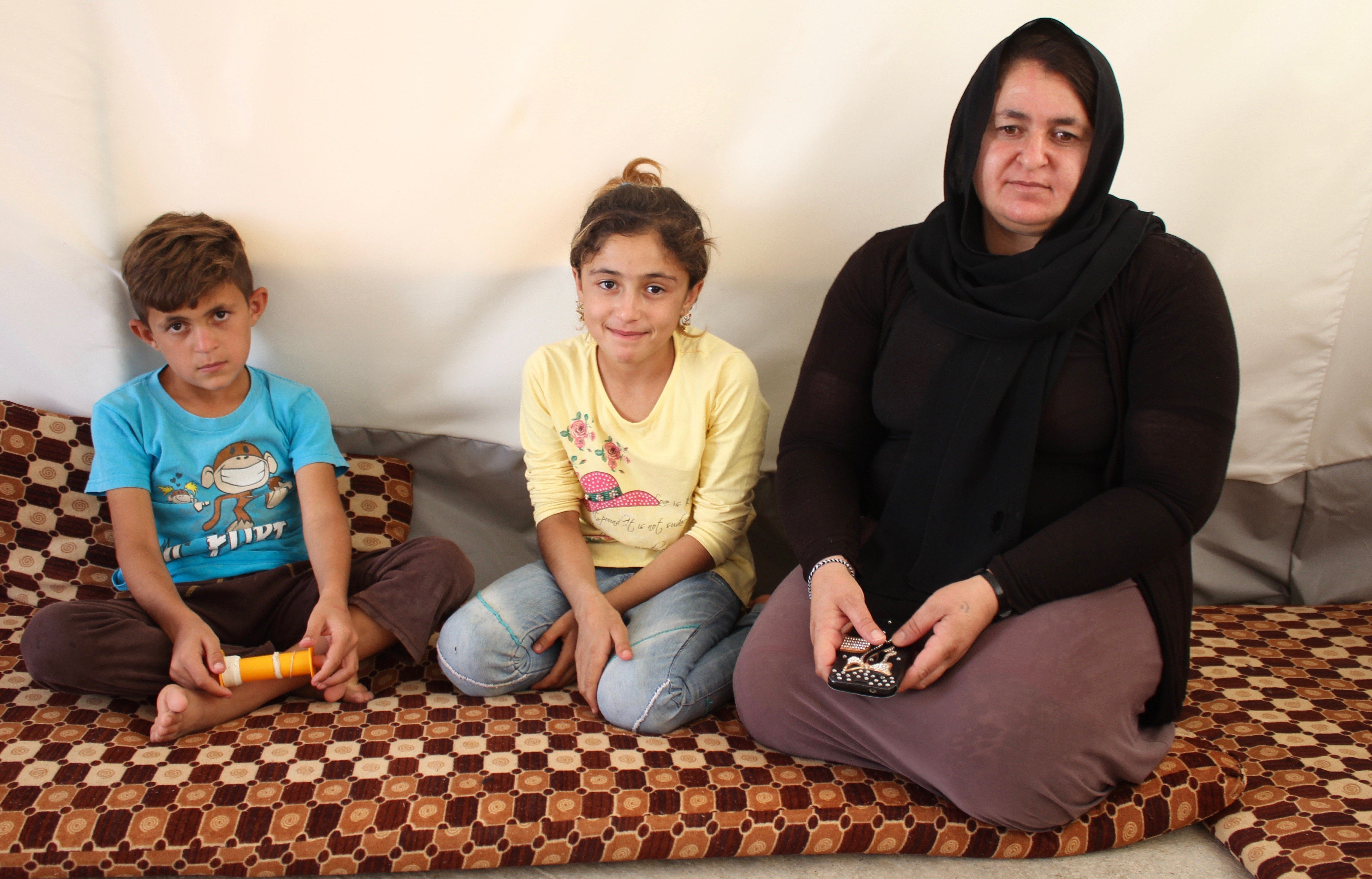 Warida, a former ISIS captive, sits with two of her children in their family tent in a northern Iraqi...